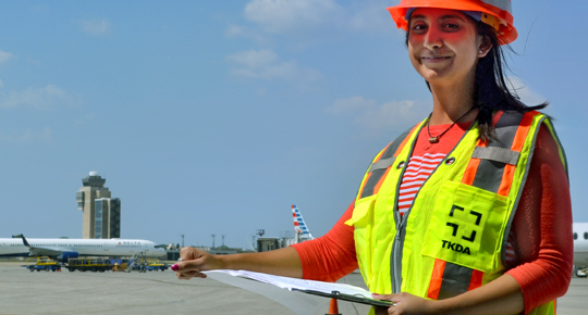 Riya Patel standing at a airport with reflective gear and helmet