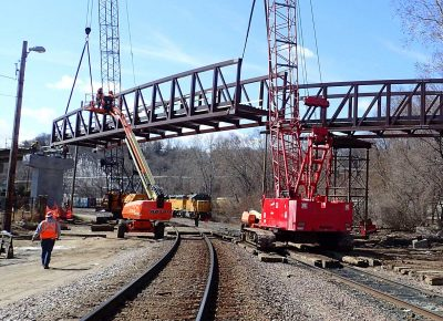 A crane putting in a section of the bridge for the Robert Piram Regional Trail.