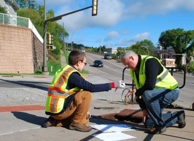 Two men working on the pavement at Mesaba Avenue in Duluth Minnesota.